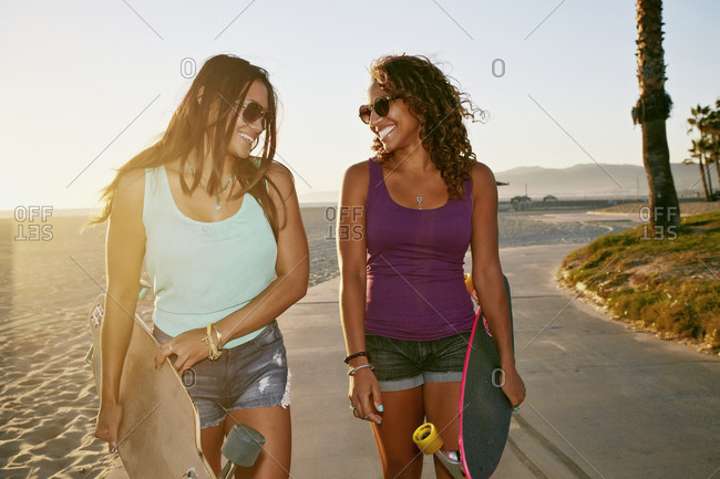 Women carrying long boards on beach