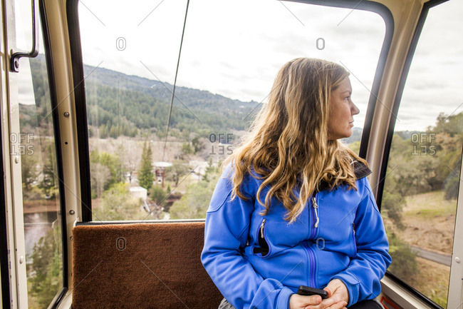 Caucasian woman riding in aerial tram