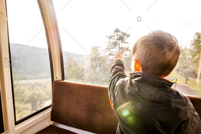Caucasian boy looking out tram window