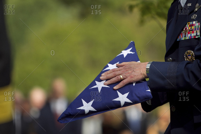 Soldier folding flag at military funeral