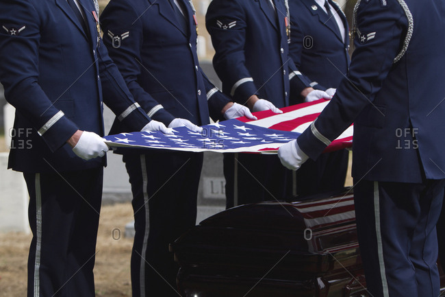 Soldiers folding flag at military funeral