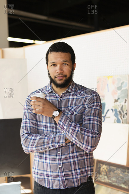 Mixed race artist drinking coffee in studio