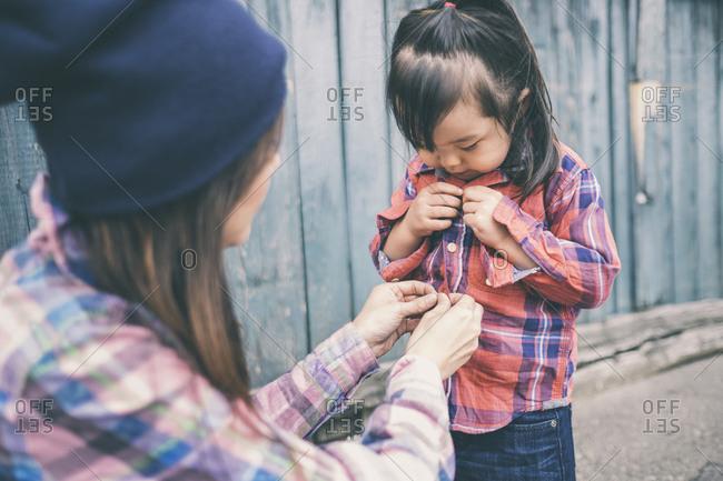 Korean mother helping daughter button her shirt