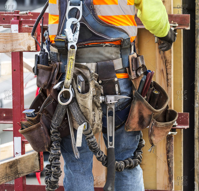 Hispanic worker wearing tool belt at construction site