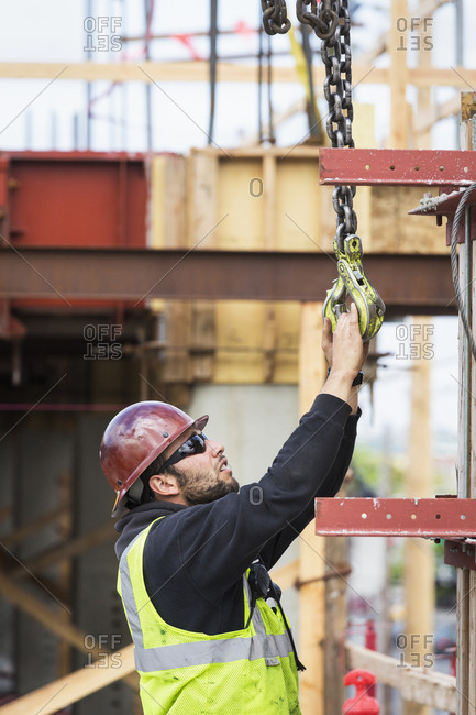 Caucasian worker holding hook at construction site