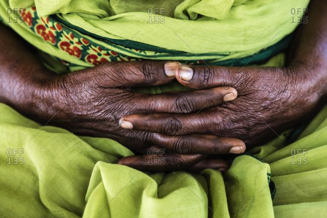 Close up of market seller's folded hands