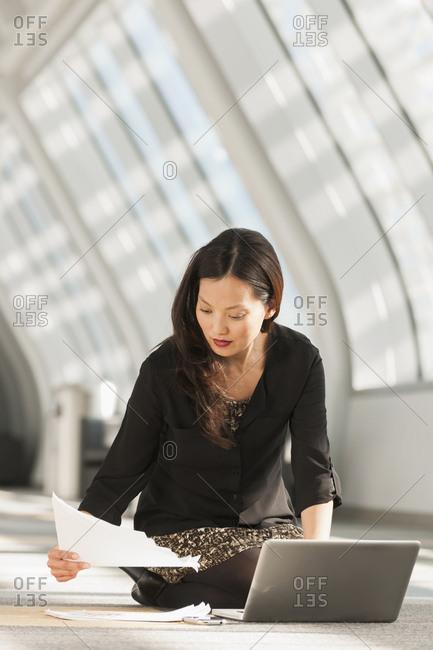 Japanese businesswoman using laptop on lobby floor