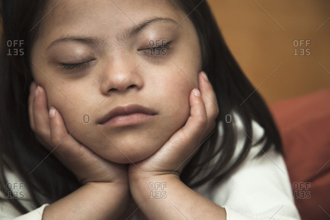 Mixed race Down syndrome girl resting with chin in hands