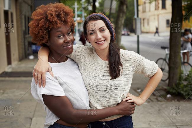 Women hugging on city street