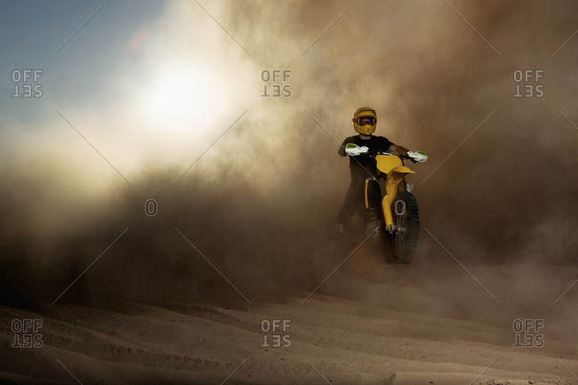 Caucasian man riding dirt bike in dust cloud