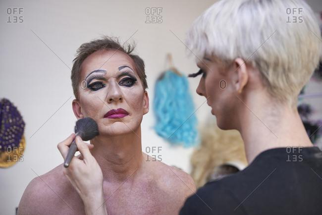 Caucasian drag queen applying colleague's makeup in bathroom