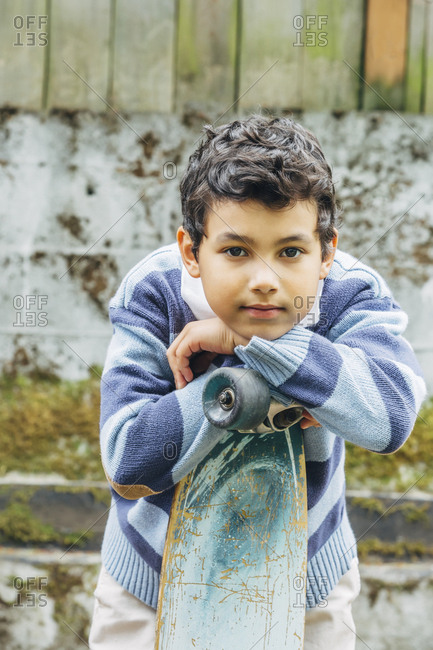 Mixed race boy leaning on skateboard outdoors