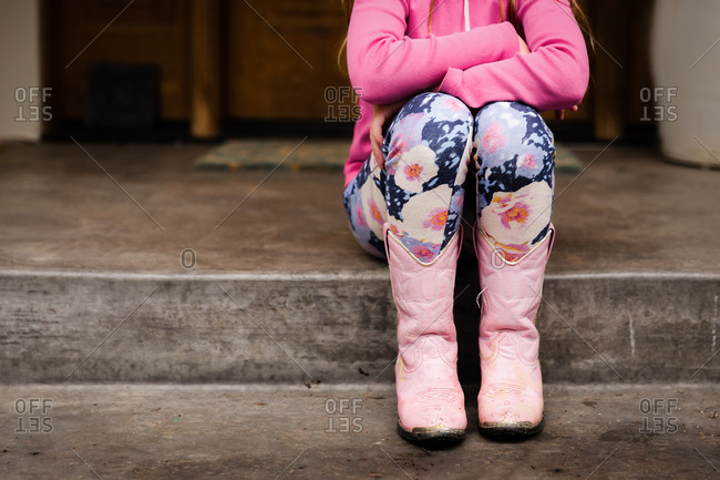 Little girl in pink cowboy boots and floral tights sitting on a step