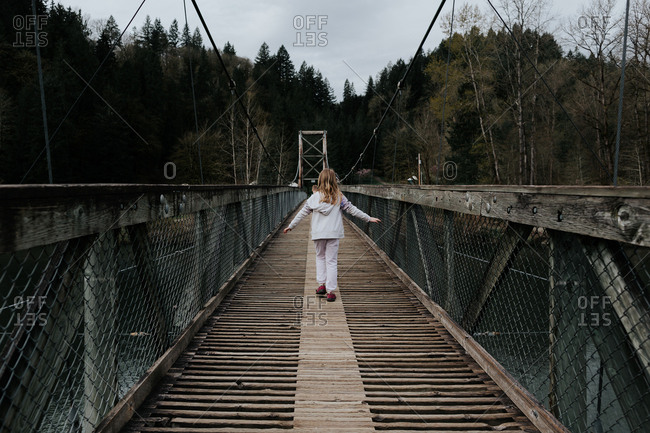 Little girl crossing a long wooden pedestrian bridge