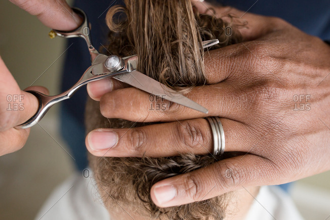 Close-up of boy's hair about to be cut with scissors during a home haircut