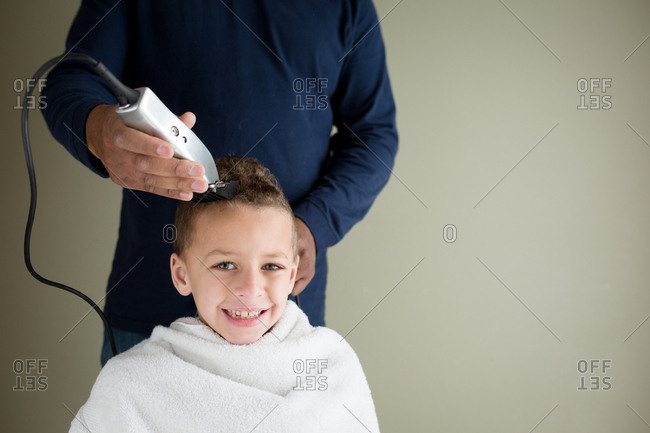 Smiling Boy Getting His Head Shaved With Clippers During A Home
