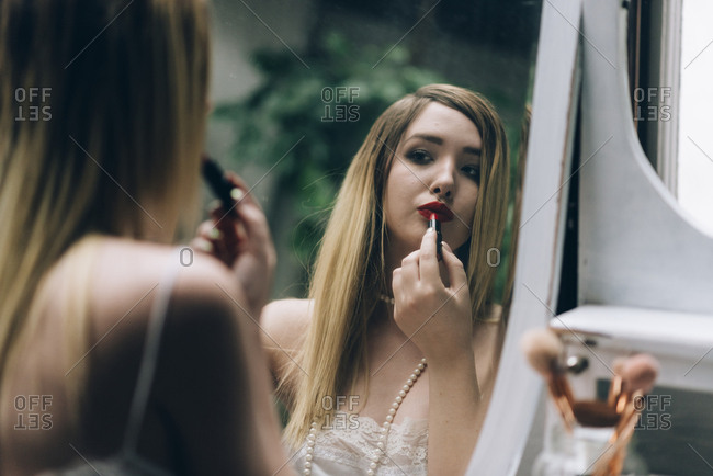 Beautiful young woman looking at vintage mirror and applying makeup on her face