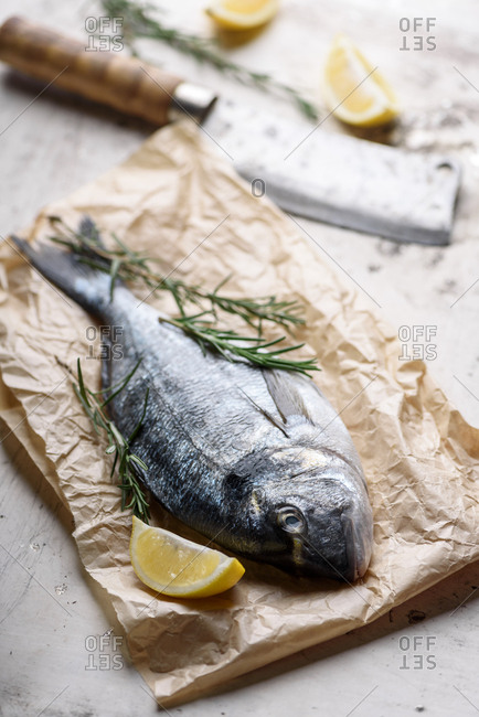 Fresh dorado fish with lemon slices and rosemary in craft paper