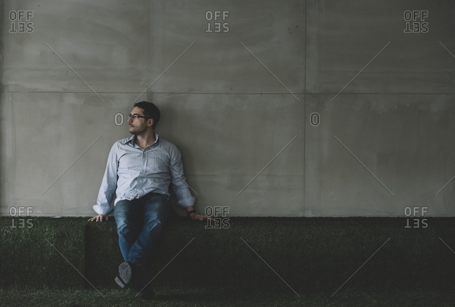 Young man in smart casual clothing sitting in front of gray wall