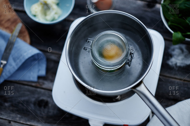 Cooking egg dish in jar on hot plate