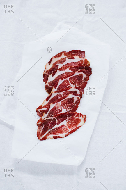 Slices of cured meat on paper