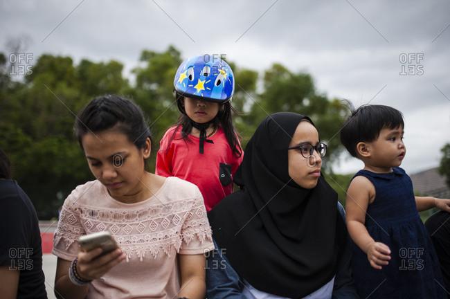 Malaysian women and boys sitting outside