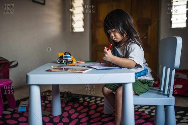 Malaysian boy drawing at table