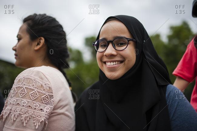 Malaysian Muslim woman sitting outside