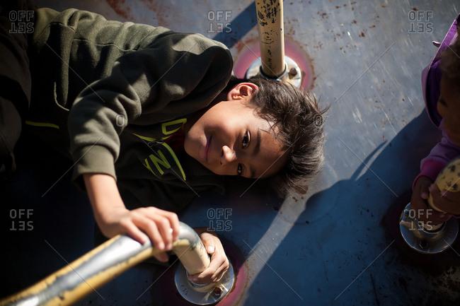 Boy lying on a merry go round