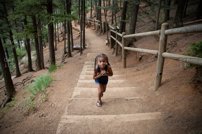 Girl walking up steps in forest