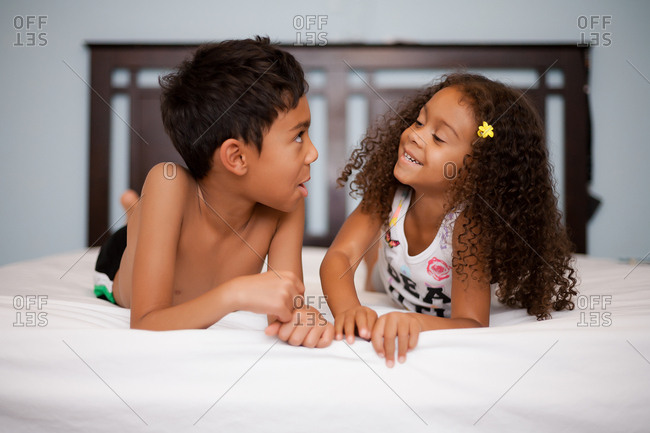 Siblings chatting together on bed