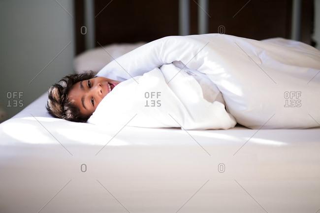 Boy smiling under a comfy blanket