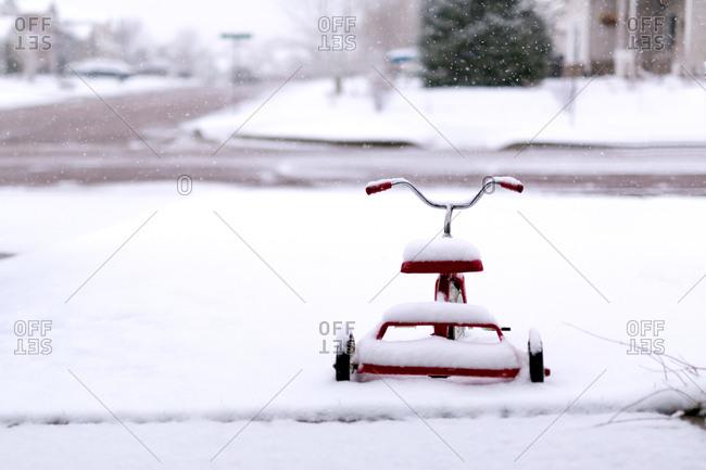 Trike buried in snow in yard
