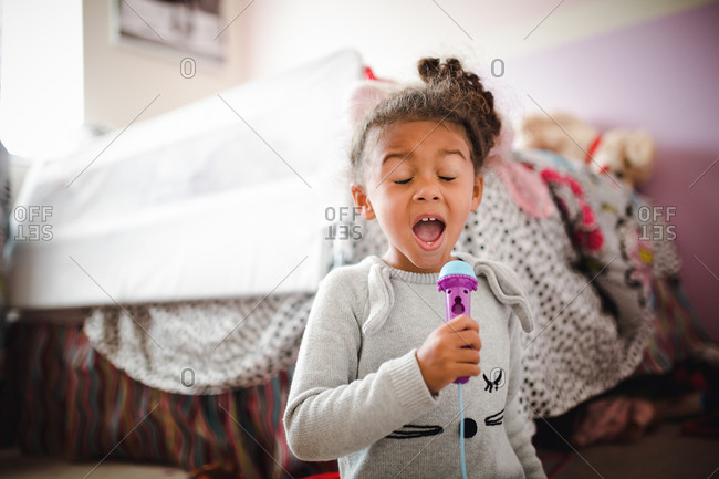 Girl singing into toy microphone