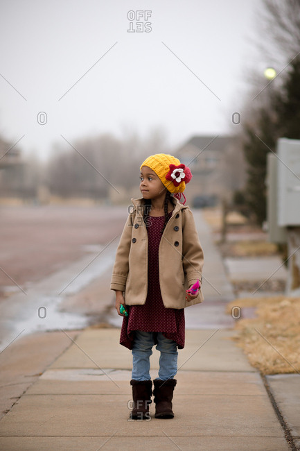 Girl standing on suburb sidewalk in winter