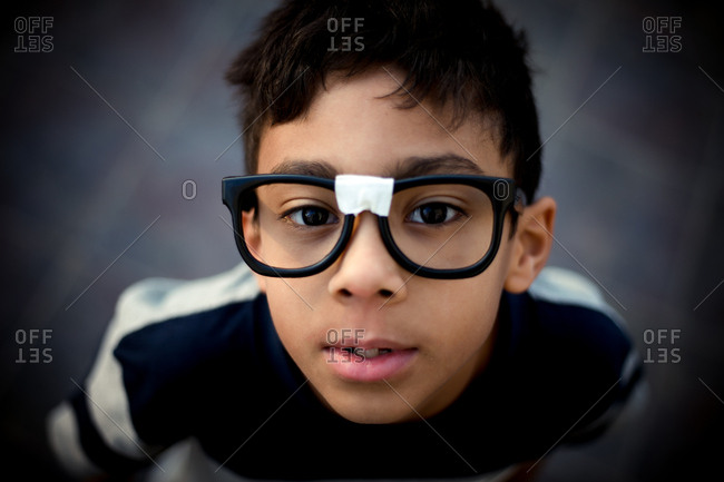 Boy wearing taped glasses