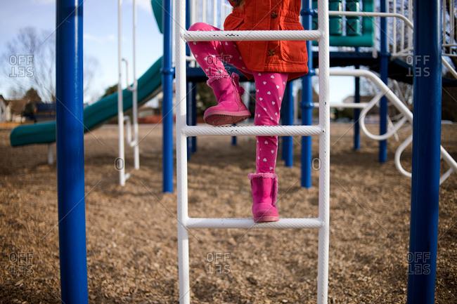 Girl climbing ladder in playground
