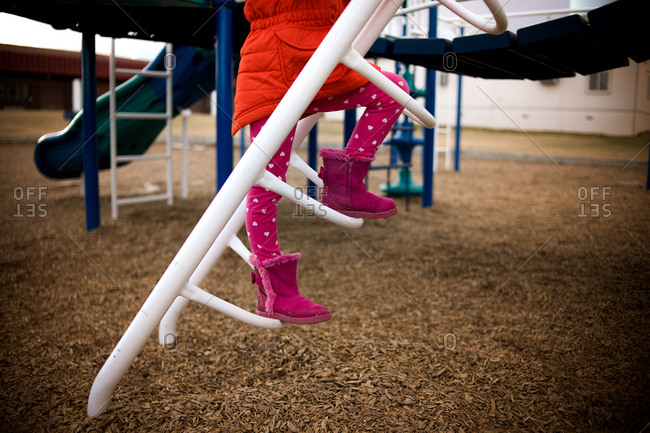 Girl climbing up ladder in playground