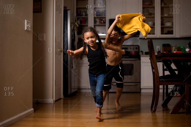 Boy and girl running around house