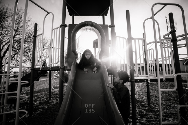 Two kids in sunlit playground