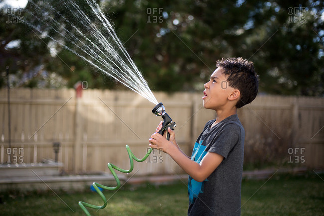 Boy watching water spray from hose