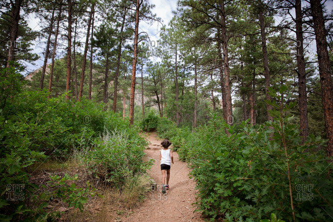 Girl running down trail in forest