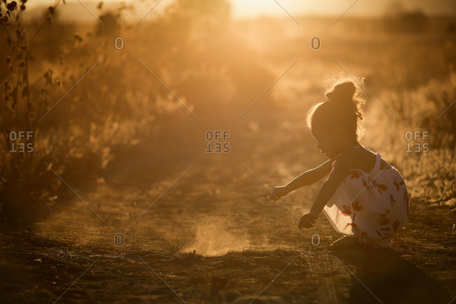 Girl playing in dirt in sunset's glow