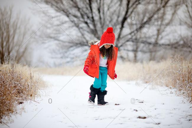 Girl wandering in snow in field