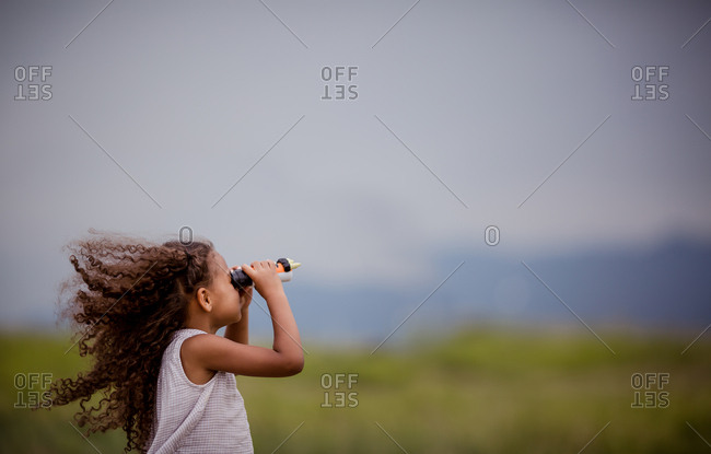 Girl with binoculars in field