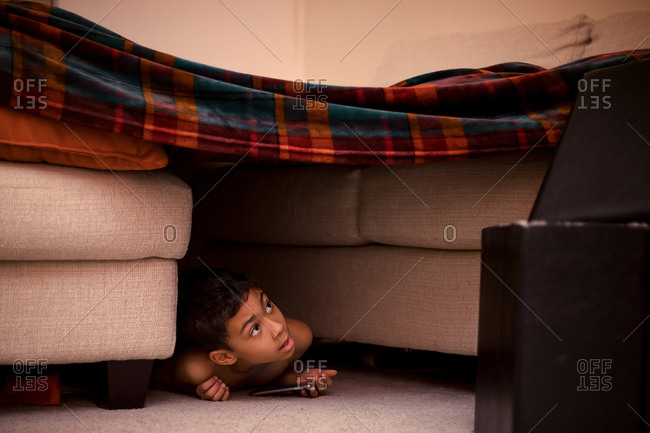 Boy in a blanket fort in home