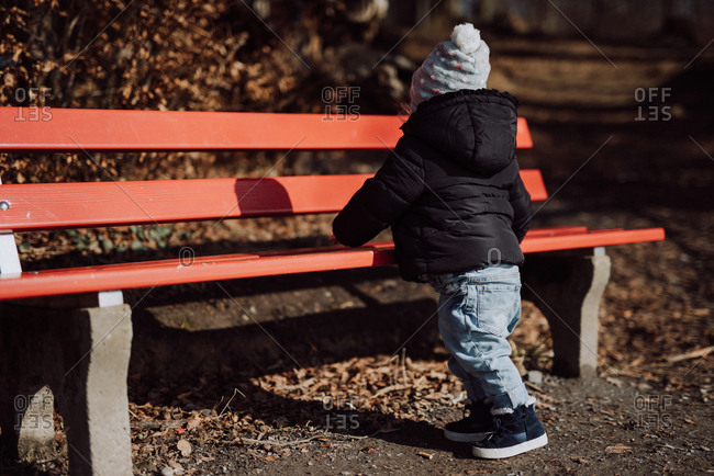 Toddler at park bench in cold weather