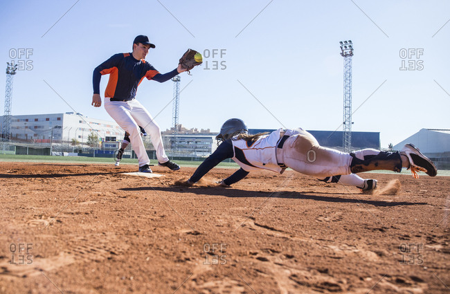 Baseball player sliding to the base during a baseball game