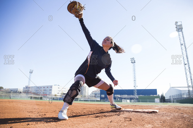 Female baseman catching the ball during a baseball game