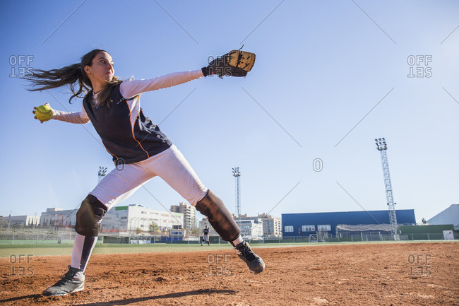 Female baseball player throwing the ball during a baseball game